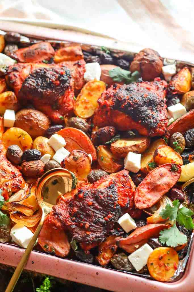 Roasted Harissa Chicken Thigs with Potatoes, feta, olives, and herbs on a sheet pan