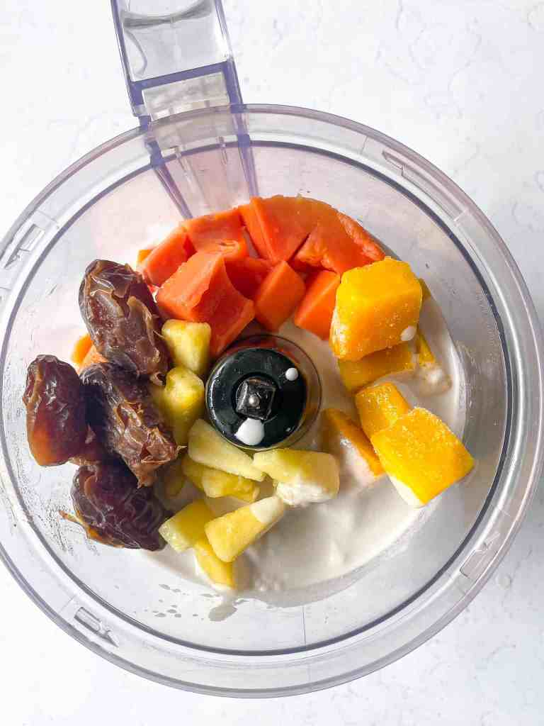 Easy Papaya Nice Cream. Papaya, pineapple, dates, mango, coconut cream ingredients in the blender to make nice cream recipe