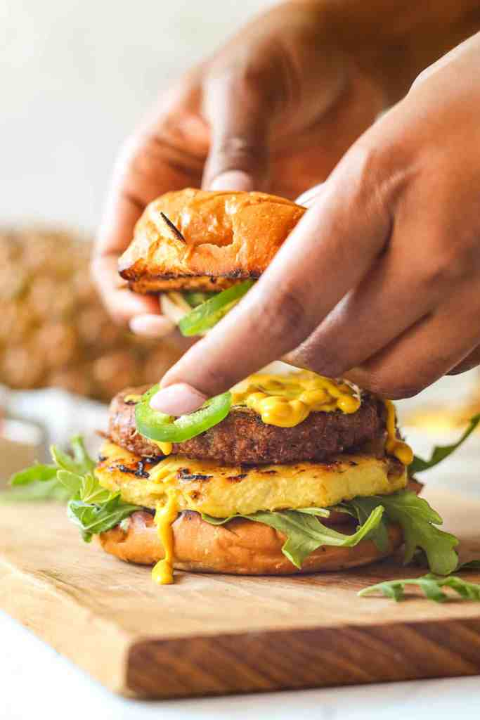 Assembling Beyond Burger with favorite toppings: mustard, jalapeno, pineapple, arugula