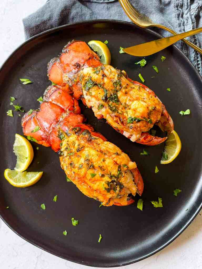 Juicy Garlic Butter Lobster Tails with lemon wedges.