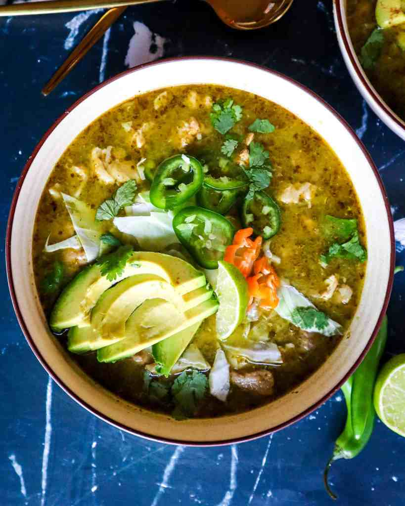 Bowl of Pork Pozole Verde with Toppings of avocado, jalapeno, lime, cabbage, and habanero