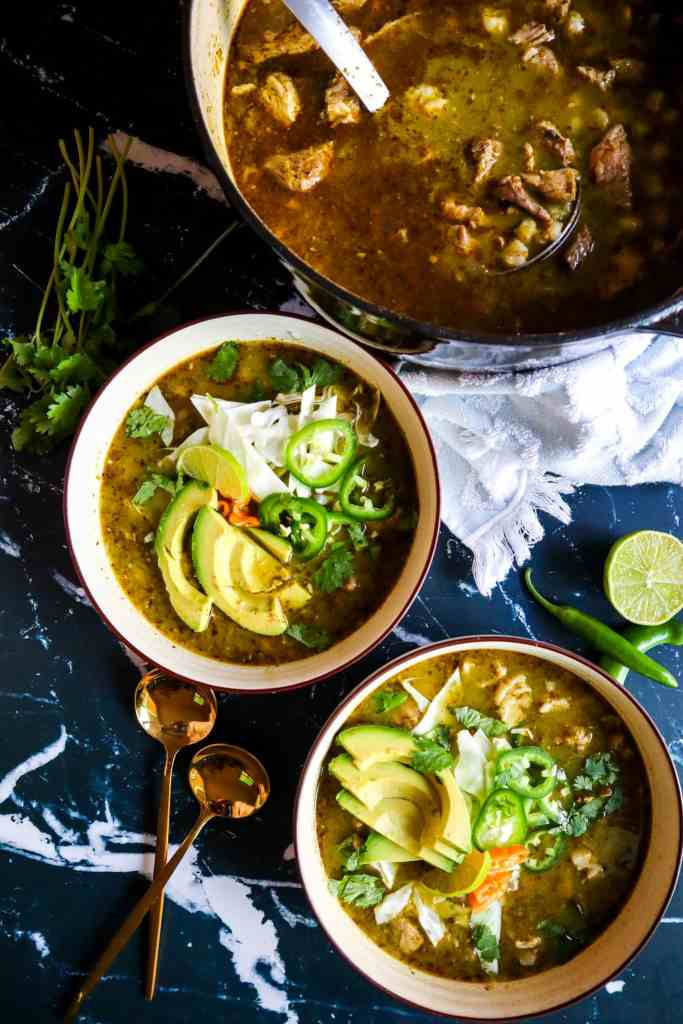 2 bowls of Pork Pozole Verde with Toppings of avocado, jalapeno, lime, cabbage, and habanero