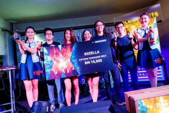 Tiger Beer marketing manager Jessie Chuah presents the mock cheque to Tiger Jams Top 3 act Rozella at her showcase on Aug 13 at The Hive, Trec.