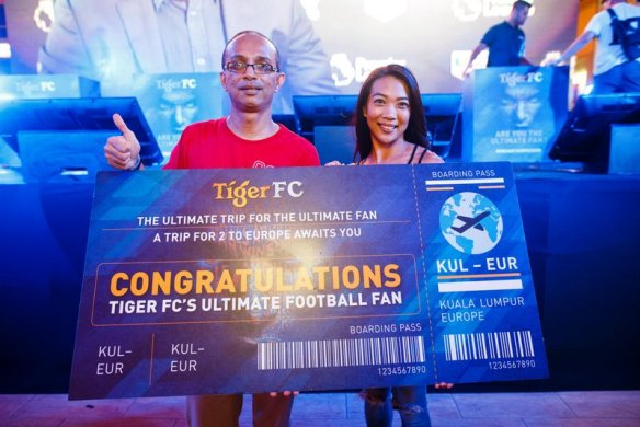 Kumaresan receiving his reward for being The Ultimate Fan from Jessie Chuah Tiger Beer Marketing Manager - a trip to Europe to watch his favourite team