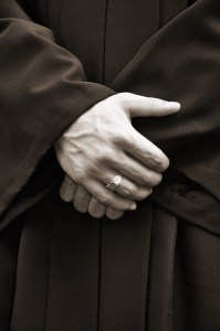 man in black robe with crossed hands