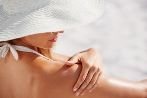 woman with healthy skin applying sunscreen to shoulder