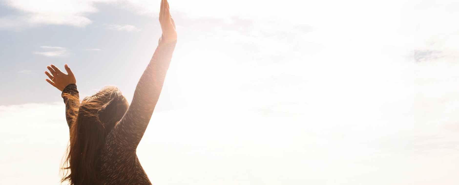 photo of woman raising both hands