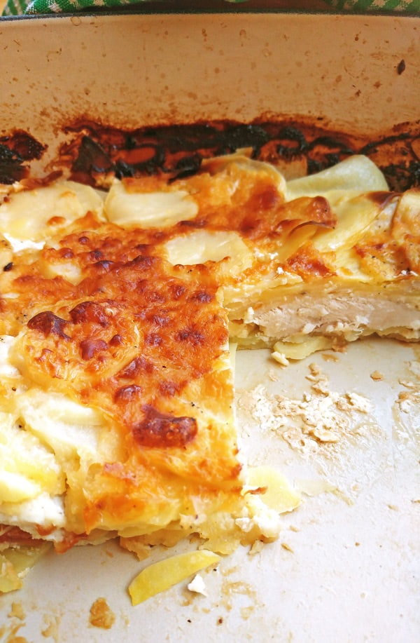 Detail of cut potato gratin in baking tray.