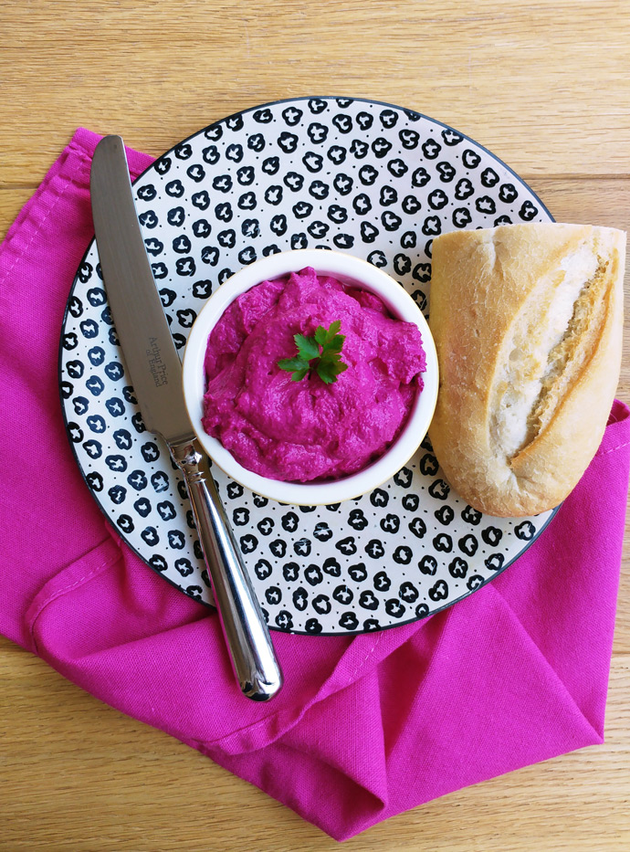 Vibrant pink beetroot spread in a small bowl on a plate with a piece of baguette and a knife.