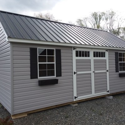 12x20 size shed with gray vinyl siding and black metal, garden style roof. Has 6 foot GGS Door with transoms and two windows with black shutters and flower boxes