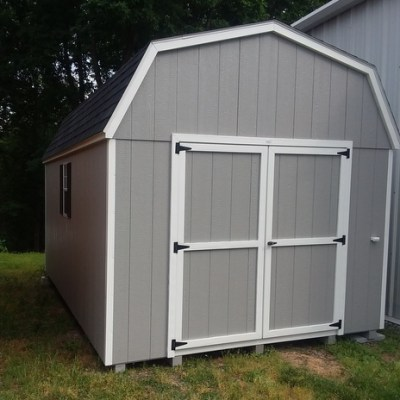 10x16 size shed, with cap gray colored painted sides and black, shingled, high barn style roof. Has a 6 foot GGS door and two windows