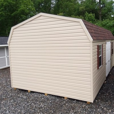 12x24 size shed with vinyl siding, brown wood colored shingles, and high barn style roof. Comes with 6 foot fiberglass doors and two windows with shutters