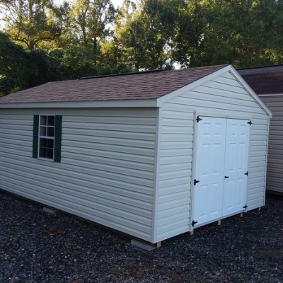 12x20 size vinyl a-roof style shed with almond siding, desert tan arch shingle roof, forest green shutters, 10' ridgevent and 6 foot fiber doors with two windows