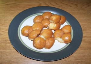 A plate filled with glazed donut holes.