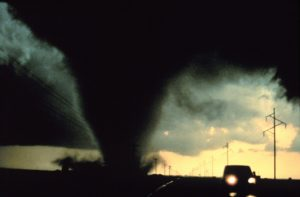 A large dark tornado and a nearby car.