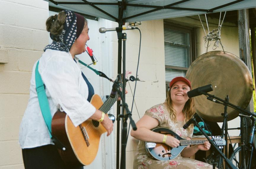 two women playing guitar outdoors and singing into microphones