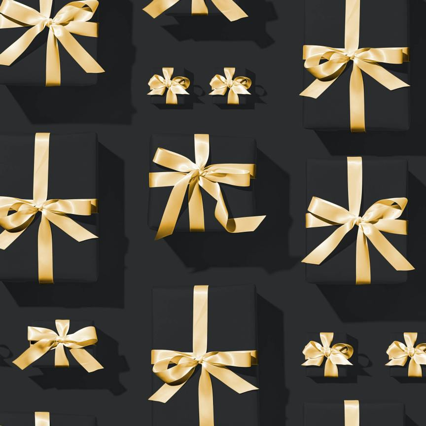 different sized black gift boxes with gold ribbon on a black background