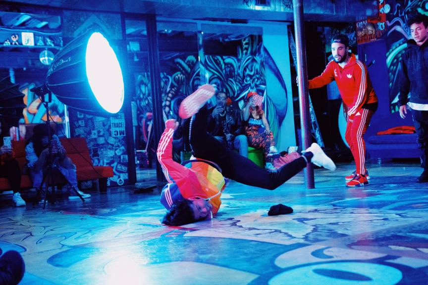 two men filming a breakdancing video in graffiti filled room