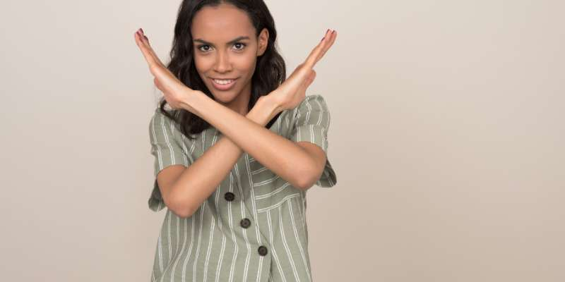 """woman crossing arms in a """"no"""" symbol in front of her chest"""