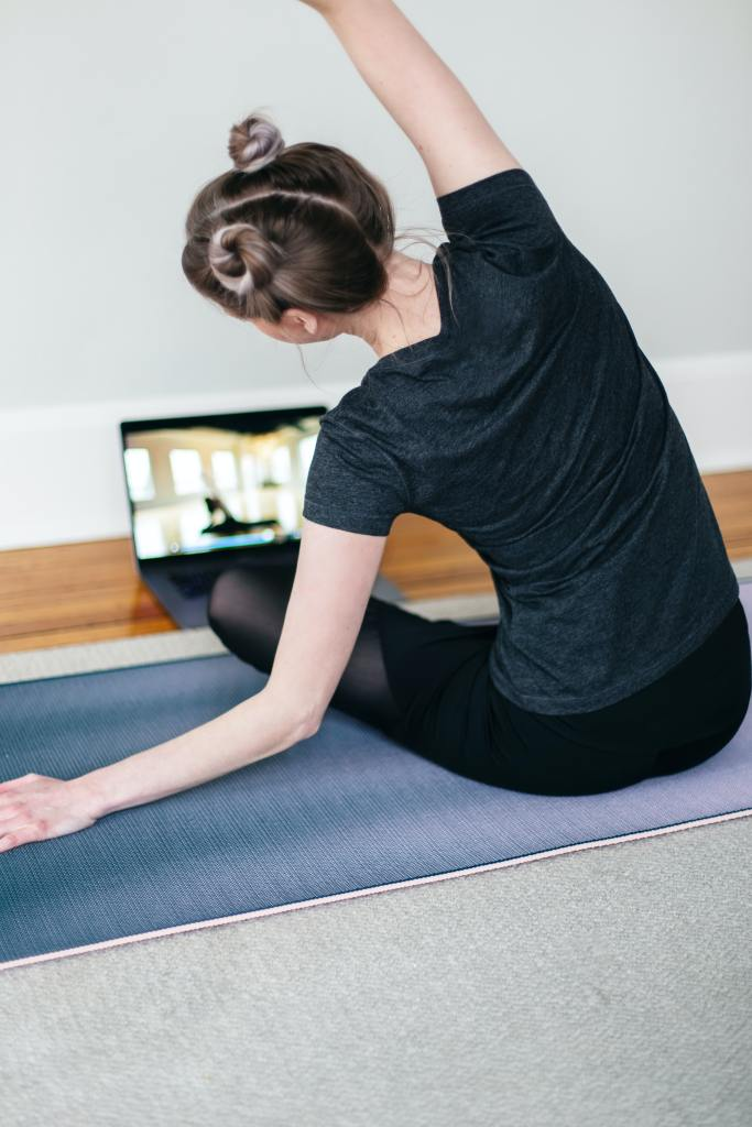 woman with hair in two buns side-bending while sitting on a yoga mat in front of laptop