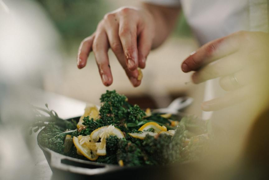 Person's hands putting the finishing touches on a kale and lemon salad