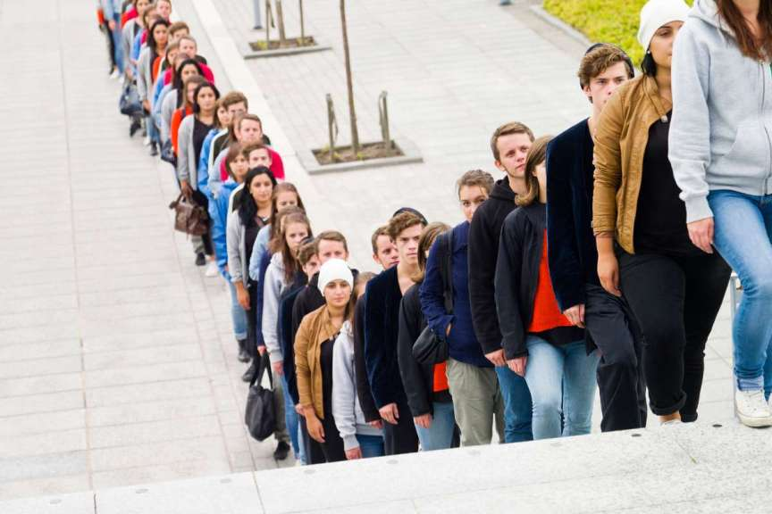 long line of people single-file winding up and down stairs