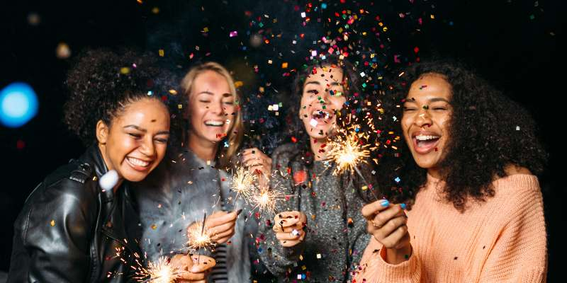 happy people playing with sparklers