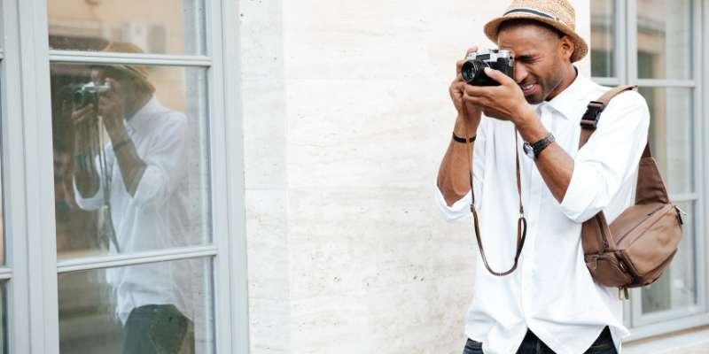 man wearing a hat taking photos
