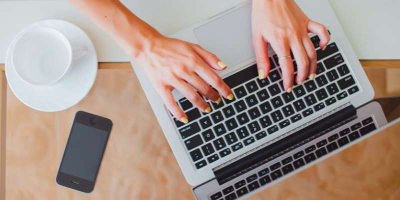 closeup of hands with yellow nail polish typing on laptop