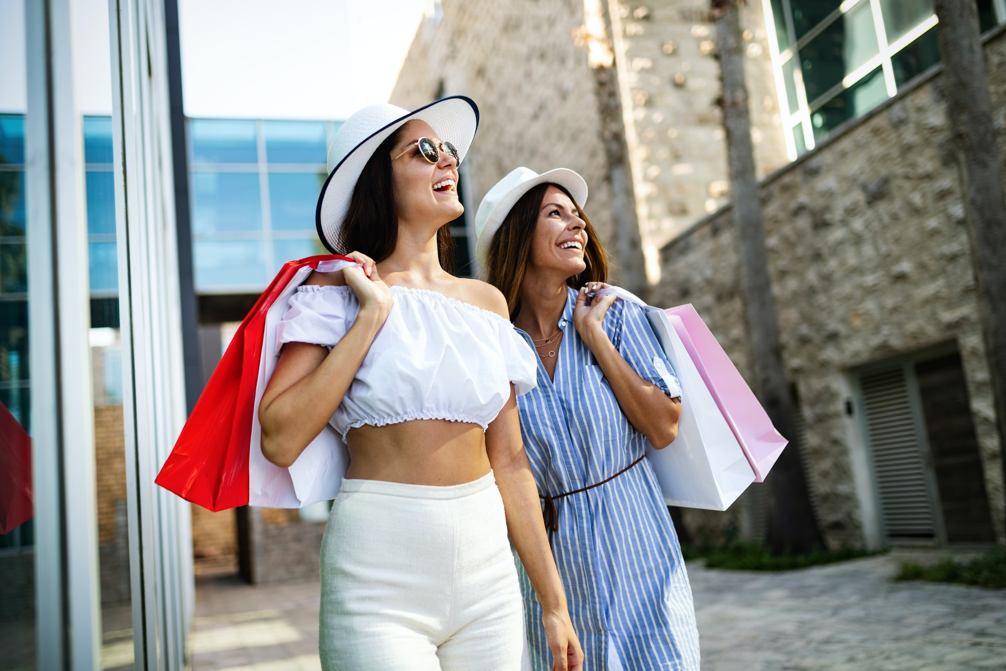 Happy friends women shopping in the city on vacation