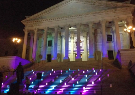 The colors of the transgender community flag are cast on the South Carolina State House during a Transgender Day of Remembrance event on Nov. 15. Photo Credit: Ryan Wilson/Facebook.