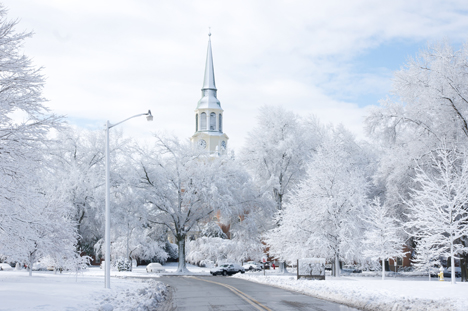 A snow-covered Wake Forest University campus, with the iconic Wait Chapel standing above the whitened canopy of trees. Photo Credit: almassengale, via Flickr. Licensed CC.
