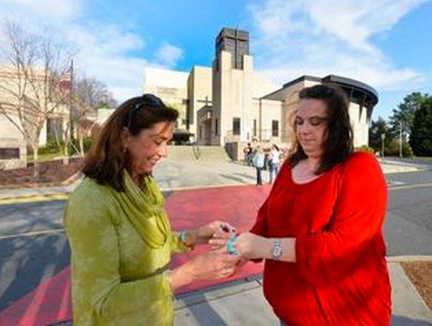 """Diane Troy (left), with PFLAG Charlotte outside Charlotte Catholic's gymnasium before the 7 p.m. meeting puts a """"We are all God's Children"""" wrist band on Katy Spiecha's (right), wrist. Photo Credit: Robert Lahser/Charlotte Observer."""