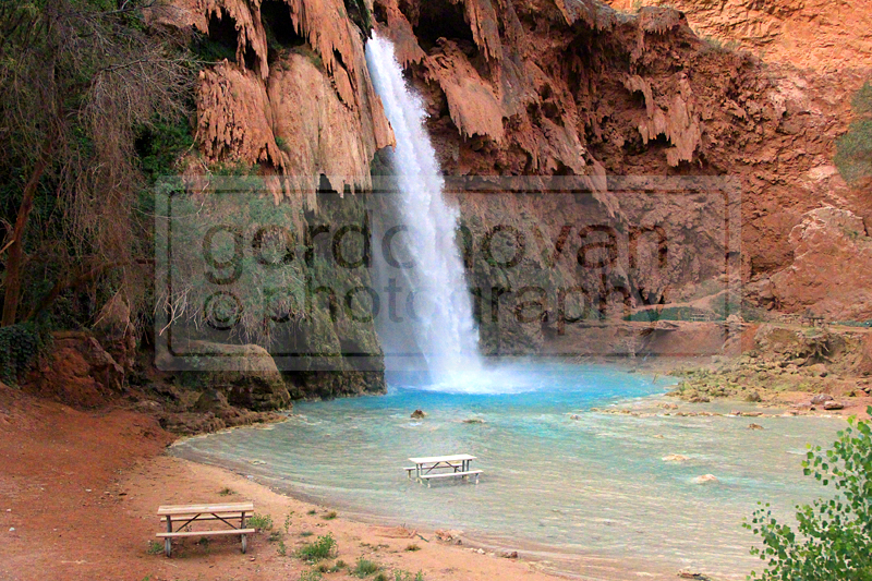 The vibrant blue water contrasts against the striking red rocks of the canyon walls as Havasu Falls plunges nearly 100 feet into a wide pool of blue-green waters.
