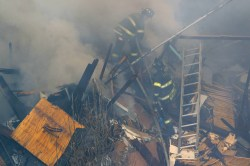 Two New York City firefighters climb on top of the remains of building that collapsed after explosion on Park Ave. and 116th Street in New York, March 12, 2014. (Gordon Donovan/Yahoo News)