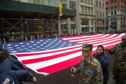 An American flag is stretched across Fifth Avenue by veterans at the start of the Veterans Day parade in New York on Nov. 11, 2014. (Gordon Donovan)