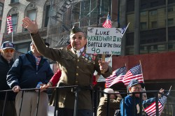 World War II veteran Luke Gaspare waves to the crowds aboard a float during the Veterans Day parade on Fifth Avenue in New York on Nov. 11, 2014. (Gordon Donovan)