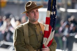A flag bearer dressed as a doughboy (WWI infantryman) pauses during the Veterans Day parade on Fifth Avenue in New York on Nov. 11, 2014.. (Gordon Donovan)