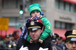 The son of a New York City Police officer get a ride as dad marches in the St. Patrick's Day parade past protesters, March 17, 2015, in New York. (Gordon Donovan)