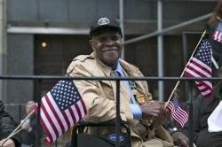 A veteran is all smiles as waves a flag on board a float up Fifth Avenue during the Veterans Day parade in New York City. (Gordon Donovan)