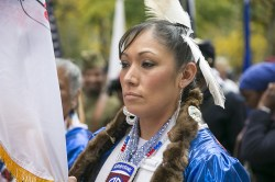 A woman in Native American garb gets ready for the parade. (Gordon Donovan)