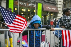 A spectator is all smiles and cheers as vets march during the Veterans Day parade on Fifth Avenue in New York on Nov. 11, 2015. (Gordon Donovan)
