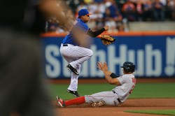 New York Mets Ruben Tejada (11) goes airborne over Boston Red Sox Xander Bogaerts (2) for the double play in the third inning of a baseball game against the Boston Red Sox at Citi Field in New York, Friday, Aug. 28, 2015. (Gordon Donovan)