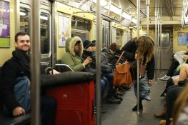 A participant of the No Pants Subway Ride remove their pants as onlookers watch on the subway in New York City, Sunday, Jan. 8, 2017. (Gordon Donovan/Yahoo News)