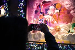A visitor takes a photo of the window display with her mobile device outside of Saks Fifth Avenue in New York City. (Gordon Donovan/Yahoo News)
