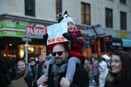 A youngster rides dad's shoulders and holds up a sign during a march in New York, Jan. 29, 2017, protesting President Donald Trump's immigration order. (Gordon Donovan/Yahoo News)