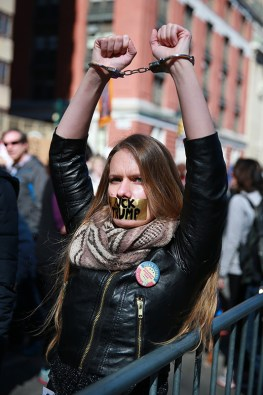 "A young woman wears handcuffs and has her mouth taped shut with the words ""F*** TRUMP"" inside police barricades at the ""Not My President's Day"" rally at Central Park West in New York City on Feb. 20, 2017. (Gordon Donovan/Yahoo News)"