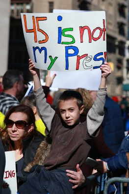 "A youngster with his mother holds up a sign during the ""Not My President's Day"" rally at Central Park West in New York City on Feb. 20, 2017. (Gordon Donovan/Yahoo News)"