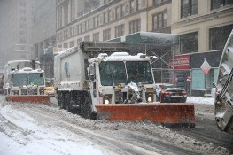New York City Sanitation trucks plow along E. 42nd Street near Grand Central Terminal in New York on Feb. 9, 2017. (Gordon Donovan/Yahoo News)