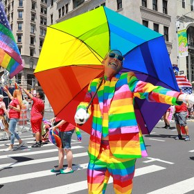 A marcher carrying an umbrella and dressed as a rainbow gestures for the camera during the N.Y.C. Pride Parade in New York on June 25, 2017. (Photo: Gordon Donovan/Yahoo News)